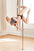 Young slim pole dance woman holding a pose — Stock Photo