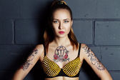 Rock style girl with tattoo stayong near brick wall — Stock Photo
