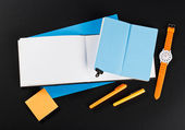 Student girl workplace. open notepads with blue and white pages. Orange stickers and orange pens with orange watches — Fotografia Stock