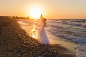 Young bride enjoys walking on a hazy beach at dusk. — Stock Photo