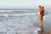 Young couple enjoys walking on a hazy beach at dusk. — Stock Photo