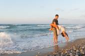 Young couple enjoys walking on a hazy beach at dusk. — Stockfoto
