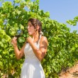 Young woman farmer tastes a glass of red wine. — Stock Photo #66024427