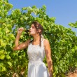 Young woman farmer tastes a glass of red wine. — Stock Photo #66024513