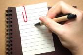 Paper with hand holding pen — Stockfoto
