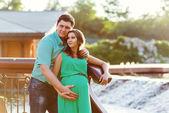 Feliz e jovem casal grávida abraçando na natureza — Foto Stock