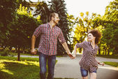 Happy couple in love running at alley. Toned image — Stock Photo