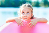 Happy girl and swim ring at the beach. toned image — Stock Photo