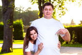 Smiling girl and man is pointing at his t-shirt — Stock Photo