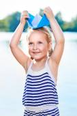 Cute little girl holding origami boat outdoors — Stock Photo