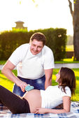 Happy husband with pregnant wife playing in nature — Stock Photo