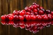 Fresh red cranberries on wooden background. Selective focus — Стоковое фото