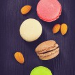 Toned photo of Colorful French macaroons on a dark rustic wooden background — Stock Photo #62630141