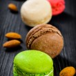 Colorful French macaroons on a dark rustic wooden background, selective focus — Stock Photo #62630161