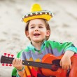 Toned photo of Little happy smiling boy plays his guitar or ukulele — Stock Photo #63190645