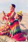 Toned photo of son and mother dressed in Mexican clothes praying together — Stock Photo