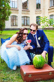 Bride and groom eating watermelon at the picnic — Stock Photo