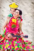 Toned photo of little boy hugging his mother in Mexican costume and playing the guitar — Stock Photo
