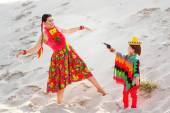 Boy dressed in Mexican costume holding a toy gun and plays with his mother — Stock Photo