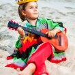 Toned photo of Little happy smiling boy plays his guitar — Stock Photo #65054109