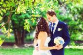 Toned photo of bride and groom outdoors park under trees — Stock Photo