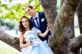 Bride and groom outdoors park under trees — Stock Photo