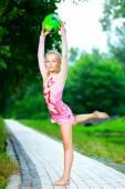 Elastyczne dziewczynka robi gimnastyka pionowego podziału z piłki gimnastyczne — Zdjęcie stockowe