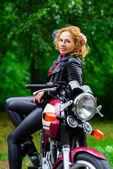 Motorcu kız bir motosiklet üzerinde deri ceketli — Stok fotoğraf