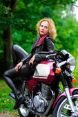 Biker girl in leather jacket on a motorcycle — Stock Photo
