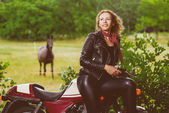 Biker girl in leather jacket on a motorcycle over the background of horse. Warm toned image — Stock Photo