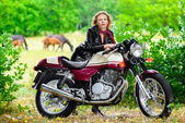 Biker girl in leather jacket on a motorcycle over the background of horses — Stock Photo