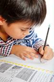 A young boy doing homework on a white background. — Stock Photo