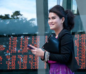 Business woman trade stock on mobile near exchange board — Stock Photo