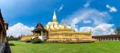Panorama shot - Laos travel landmark, golden pagoda wat Phra That Luang in Vientiane. Buddhist temple. Famous tourist destination in Asia. — ストック写真