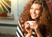 Young smiling woman sitting holding hot drink in an outside setting — Stock Photo