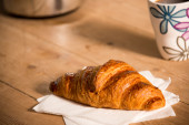 Croissant and mug of coffee on table — Stock Photo