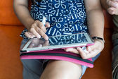 Woman sitting on sofa and using tablet — Stock Photo