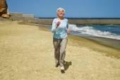Elderly happy woman running on the beach along the coast near the sea — Stock Photo