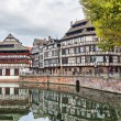 Traditional half-timbered houses reflecting in water, Strasbourg — Stock Photo #58339795