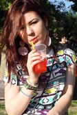 Young lady eating slush in the park — Stock Photo
