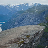 A vibrant picture of famous norwegian hiking place - trolltunga, the trolls tongue, rock skjegedall, with a tourist, and lake ringedalsvatnet and mountain panoramic scenery epic view, Norway — Stock Photo