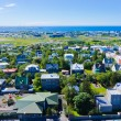 Beautiful super wide-angle aerial view of Reykjavik, Iceland with harbor and skyline mountains and scenery beyond the city, seen from the observation tower of Hallgrimskirkja Cathedral. — Stock Photo #61779207