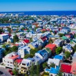 Beautiful super wide-angle aerial view of Reykjavik, Iceland with harbor and skyline mountains and scenery beyond the city, seen from the observation tower of Hallgrimskirkja Cathedral. — Stock Photo #61779243