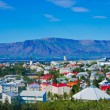 Beautiful super wide-angle aerial view of Reykjavik, Iceland with harbor and skyline mountains and scenery beyond the city, seen from the observation tower of Hallgrimskirkja Cathedral. — Stock Photo #61779335