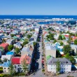 Beautiful super wide-angle aerial view of Reykjavik, Iceland with harbor and skyline mountains and scenery beyond the city, seen from the observation tower of Hallgrimskirkja Cathedral. — Stock Photo #61779775