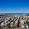 Beautiful super wide-angle aerial view of Reykjavik, Iceland with harbor and skyline mountains and scenery beyond the city, seen from the observation tower of Hallgrimskirkja Cathedral. — Stock Photo #61779921