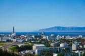 Beautiful super wide-angle aerial view of Reykjavik, Iceland with harbor and skyline mountains and scenery beyond the city, seen from the observation tower of Hallgrimskirkja Cathedral. — Stock Photo