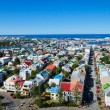 Beautiful super wide-angle aerial view of Reykjavik, Iceland with harbor and skyline mountains and scenery beyond the city, seen from the observation tower of Hallgrimskirkja Cathedral. — Stock Photo #61780017