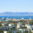 Beautiful super wide-angle aerial view of Reykjavik, Iceland with harbor and skyline mountains and scenery beyond the city, seen from the observation tower of Hallgrimskirkja Cathedral. — Stock Photo #61780305