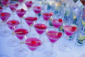 Beautiful line of different colored cocktails with smoke on a Christmas party, tequila, martini, vodka, and others on decorated catering bouquet table on open air party — ストック写真